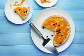 Piece of homemade orange tart on plate, on color wooden background