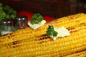 Delicious golden grilled corn with butter on table on wooden background