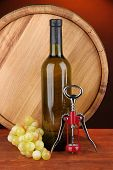 Composition of corkscrew and bottle of wine, grape, wooden barrel  on wooden table on dark backgroun