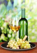 Wine bottle and glass of wine on tray, on bright background