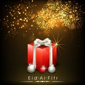 Shiny red gift box with silver ribbon on golden fireworks night for muslim community festival celebrations Eid-Al-Fitr.