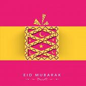 Shiny gift box wrapped in yellow ribbon on pink and yellow background for muslim community festival Eid Mubarak celebrations.