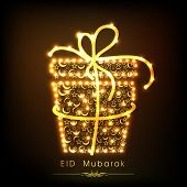 Golden gift box decorated with floral design on brown background for Muslim community festival Eid M