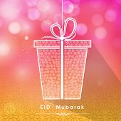 Beautiful gift box on shiny pink and yellow background for muslim community festival Eid Mubarak cel