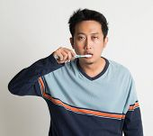 Southeast Asian male brushing teeth with sleepy eyes in a morning, on plain background