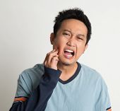Asian male toothache with painful expression, on plain background.