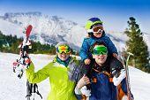 Parents and child on dad's shoulders in ski masks