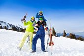 Mom, dad with child on his shoulders in ski masks