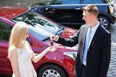 Salesman Handing Key To Woman By New Car