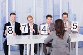 Business People Showing Score Cards In Front Of Female Candidate