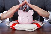 Businessman Sheltering Piggybank With Lifebelt At Desk