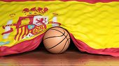 Basketball ball with flag of Spain on parquet floor