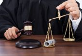 stock photo of striking  - Midsection of male judge striking gavel while holding scale with money in courtroom - JPG