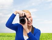 photography, technology, summer and people concept - smiling young woman taking picture with digital camera over blue sky and grass background