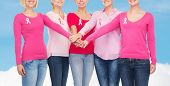 healthcare, people, gesture and medicine concept - close up of smiling women in blank shirts with pink breast cancer awareness ribbons putting hands on top over blue sky and white cloud background
