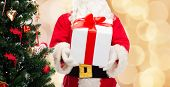 christmas, holidays and people concept - close up of santa claus with gift box and tree over beige lights background