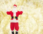 christmas, holidays and people concept - man in costume of santa claus having fun over yellow lights background