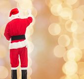 christmas, holidays and people concept - man in costume of santa claus writing something from back over beige lights background