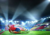Football player at stadium sliding to kick the ball