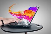 Hands of woman using laptop and colorful splashes on screen