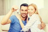 real estate, family and couple concept - smiling couple holding keys at home