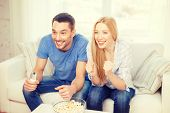food, love, family, sports, entertainment and happiness concept - smiling couple with popcorn cheering sports team at home