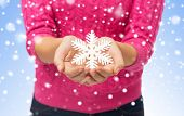 christmas, holidays and people concept - close up of woman in pink sweater holding snowflake decoration over blue background with snow