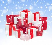 holidays, winter, birthday and celebration concept - many christmas presents over blue background with snow