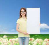 vision, health, advertisement and people concept - smiling little girl wearing eyeglasses with white blank board
