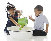 Two young siblings playing with a watering can in a tub of water.  On a white background.