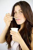 Closeup Of Cute Brunette Eating Yogurt