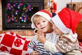 Portrait Of Two Little Sibling Boy In Santa Hats, Indoor