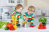 Two Funny Twin Kids Cooking Italian Meal With Spahetti