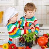 Two Funny Little Boys Cooking Italian Soup And Meal With Fresh Vegetables