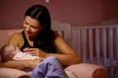 Mother At Home Cuddling Newborn Baby In Nursery