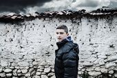 image of loam  - sad young boy before old loam wall - JPG