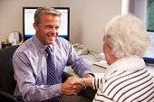 Doctor Greeting Senior Female Patient With Handshake