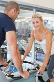 Side view portrait of smiling fit couple working on exercise bikes at the gym