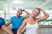 Portrait of a young couple stretching necks in yoga class