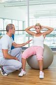 Male trainer assisting woman with abdominal crunches at the gym