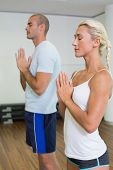 Sporty young couple with joined hands and eyes closed at fitness studio