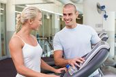 View of a male trainer assisting woman with treadmill screen options at the gym