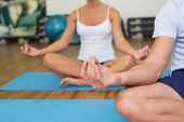 Close up of a sporty young couple sitting in lotus posture at fitness studio