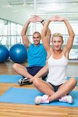 Portrait of happy young couple stretching up hands in yoga class