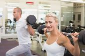 Side view of a sporty young couple lifting barbells in the gym