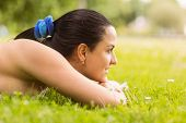 Happy fit brunette lying on the grass in the park
