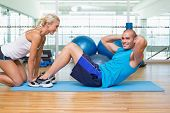 Side view of a female trainer assisting young man with abdominal crunches at fitness studio