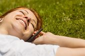 Pretty redhead calling and lying on grass at summer