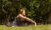 Pretty redhead smiling stretching in park on a sunny day
