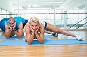 Portrait of a sporty young couple doing pilate exercises at fitness studio